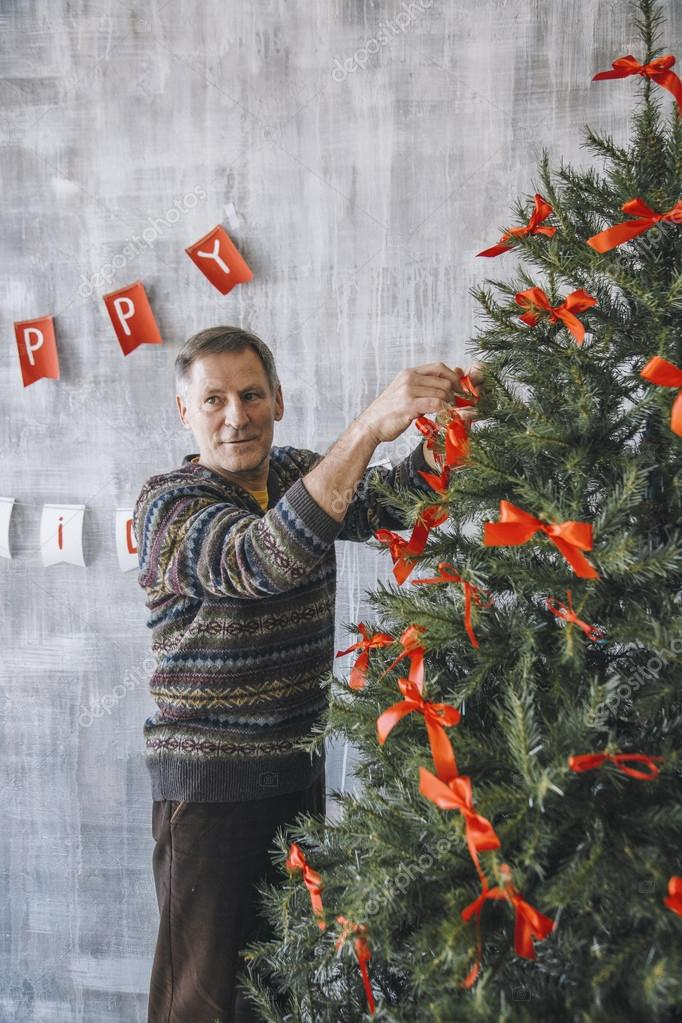 Warum Schmückt Man Den Weihnachtsbaum.Mann Schmückt Weihnachtsbaum Mit Roten Bändern Stockfoto