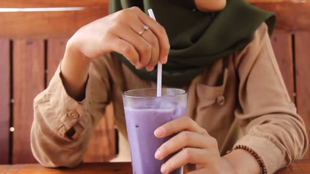 a woman is enjoying purple ice in a wooden cafe. the womans hand stirs the fresh iced grapes