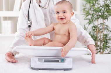 Happy smiling baby in pedrician office, measuring weight