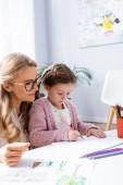 holčička kreslení obrázků s barevnými tužkami při návštěvě psycholog