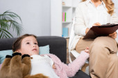 little girl lying on sofa with toy while telling problem to psychologist