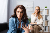 brunetka žena gestikulující a vyprávějící příběh terapeutovi