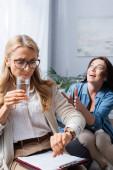 blondýny žena terapeut pitné vody a kontrolu času, zatímco bruneta žena vyprávění příběh s posedlostí