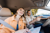 Smiling man pointing away near wife with map in car during trip