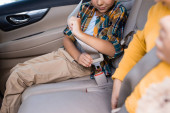 Cropped view of boy locking safety belt near sister on blurred foreground in car
