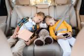 Děti s chytrým telefonem, knihou a měkkou hračkou spící v autě během cesty