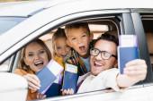 Fröhliche Familie mit Kindern im Besitz von Pässen mit Flugtickets im verschwommenen Vordergrund im Auto