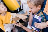 Usmívající se chlapec drží hračka letadlo v blízkosti matky s pasy a letenky na rozmazaném pozadí