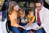 Usmívající se děti ukazující prstem na mapu poblíž rodičů v kufru auta