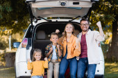 Cheerful family showing yes gesture near trunk of car outdoors