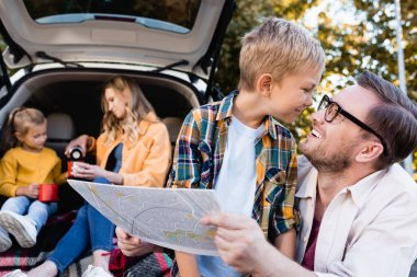 Smiling man holding map near son and wife with daughter near car on blurred background stock vector