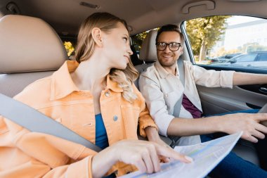 Smiling man looking at wife pointing at map on blurred foreground in car stock vector