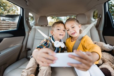 Children with headphones and toy taking selfie on smartphone on blurred foreground in car stock vector