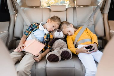 Kids with smartphone, book and soft toy sleeping in auto during travel stock vector