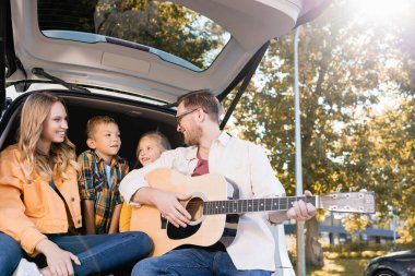 Smiling father playing acoustic guitar near wife and kids in car trunk stock vector