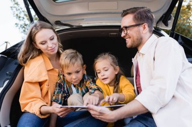 Kids pointing at map near smiling parents in trunk of auto stock vector