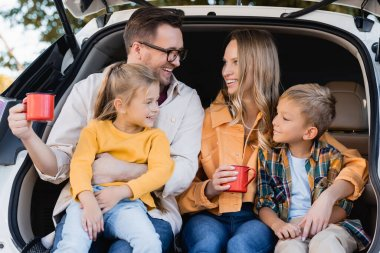 Smiling parents with cups hugging kids in trunk of car stock vector