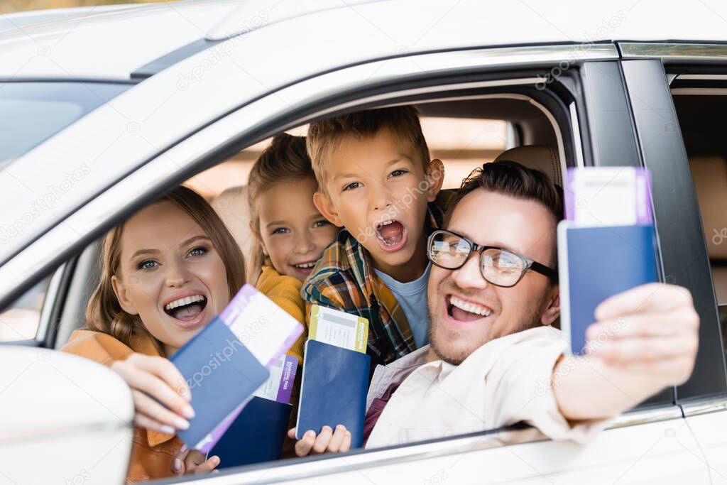 Cheerful family with kids holding passports with air tickets on blurred foreground in car stock vector