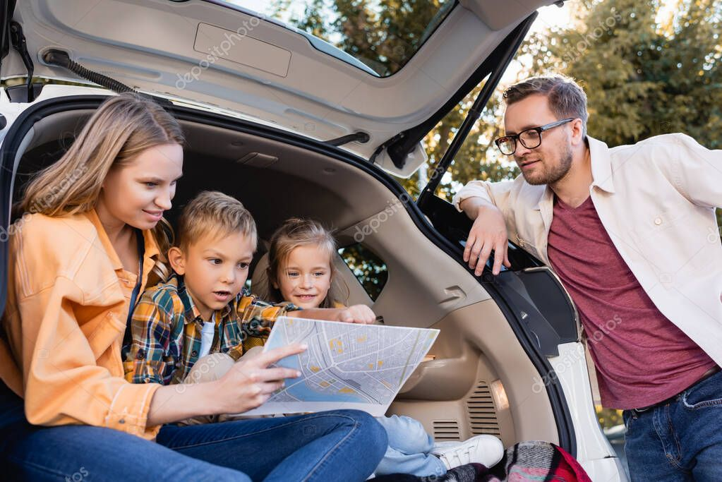 Smiling family looking at map near trunk of car during vacation stock vector