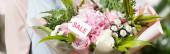 ořezaný pohled na květinářství držící kytici s nápisem na etiketě, banner