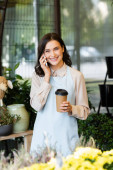 cheerful florist talking on smartphone and holding coffee to go near blurred flowers on foreground