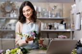 usmívající se květinářství drží eustomu květiny v blízkosti notebooku na rozmazané popředí