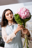 Focused female florist composing bouquet with blooming hydrangea in flower shop on blurred foreground