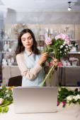 Florist composing bouquet with rose, hydrangea and chrysanthemums, while looking at laptop on desk on blurred background