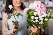 Vágott kilátás női virágárus rózsa kompozíció csokor hortenzia és krizantém homályos háttér