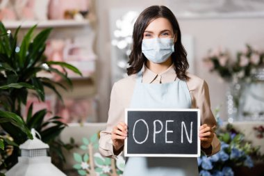 Positive florist in medical mask holding board with open lettering in flower shop near plants on blurred background stock vector