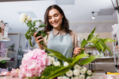 Happy female florist composing bouquet with plant and roses with blurred flowers on foreground stock vector
