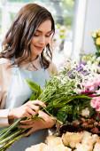 Mosolygó női virágárus gazdaság csokor krizantém és celózia homályos virágok a háttérben
