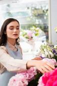 Barna nő virágárus törődő virágok közelében állvány áruház homályos ablak a háttérben