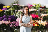 Smiling female florist with crossed arms looking at camera, while standing near racks of flowers on background