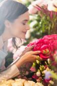 Oldalnézet boldog női virágárus csukott szemmel illatos rózsa homályos tartományban virágok a háttérben