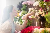 Oldalnézet boldog női virágárus törődő rózsák közelében virág tartomány elmosódott előtérben