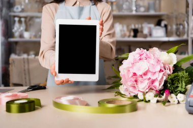 Cropped view of florist showing digital tablet with blank screen near bouquet on desk on blurred background stock vector