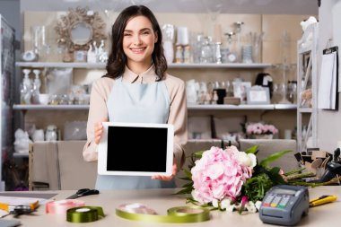 Happy florist showing digital tablet near bouquet on desk with blurred racks of vases on background stock vector