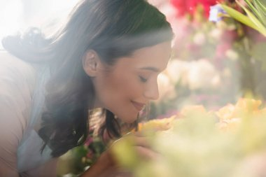 Side view of smiling female florist with closed eyes smelling flower on blurred foreground stock vector