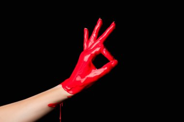 Cropped view of hand painted in red paint showing ok sign isolated on black stock vector