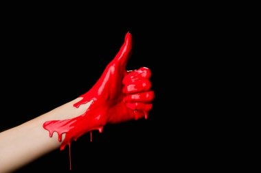 Cropped view of hand painted in red paint showing thumb up isolated on black stock vector