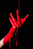 partial view of painted hand with red dripping paint isolated on black