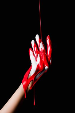 Partial view of white painted hand with red dripping paint isolated on black stock vector