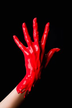 Partial view of painted hand with red dripping paint isolated on black stock vector