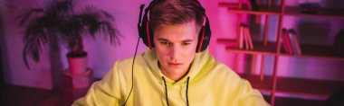 Gamer in headset with microphone looking away at home, banner