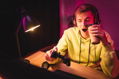 KYIV, UKRAINE - AUGUST 21, 2020: Gamer in headset yawning while holding joystick and coffee to go near computer on blurred foreground stock vector