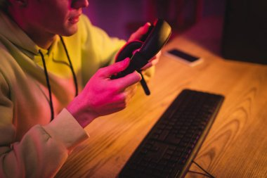 Cropped view of gamer holding headset near computer keyboard on blurred background stock vector