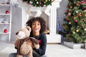 aufgeregtes afrikanisch-amerikanisches Mädchen blickt in die Kamera, während es Teddybär in der Nähe von dekoriertem Kamin und Weihnachtsbaum auf verschwommenem Hintergrund hält