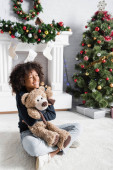 excited african american girl sitting on floor with closed eyes and embracing teddy bear near fireplace and christmas tree