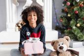 šťastný africký americký dívka dívá na kameru při držení dárek v blízkosti vánoční strom a krb na rozmazaném pozadí